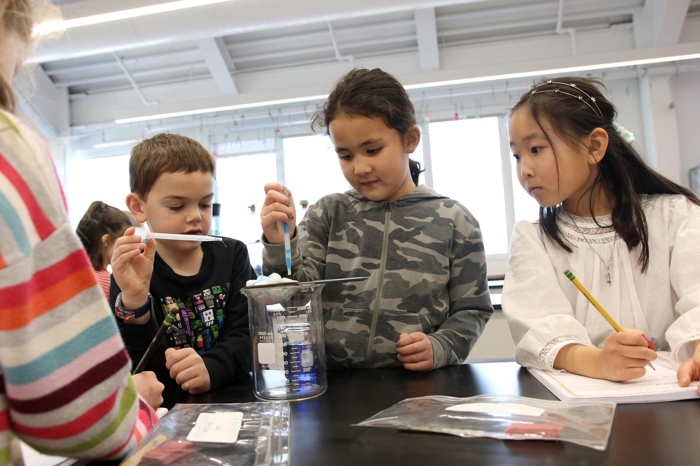 Three first graders work on a science experiment