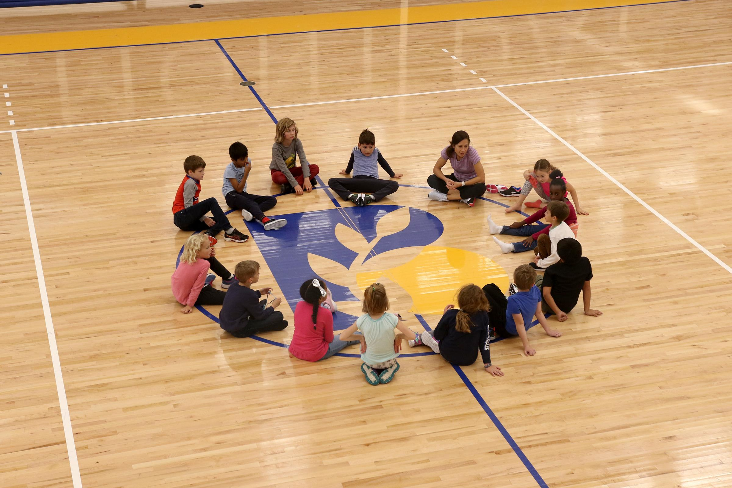 Students sit in circle during PE class