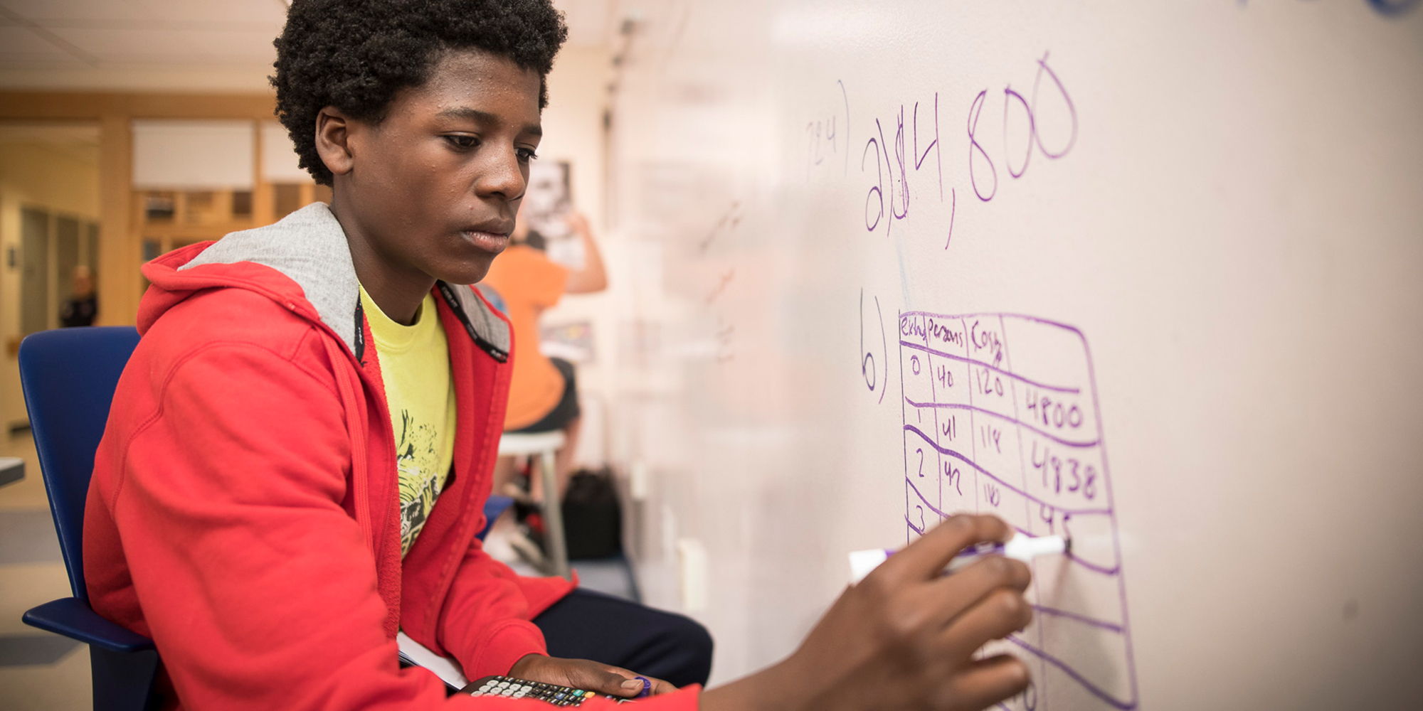 A boy works out a math problem at the whiteboard.