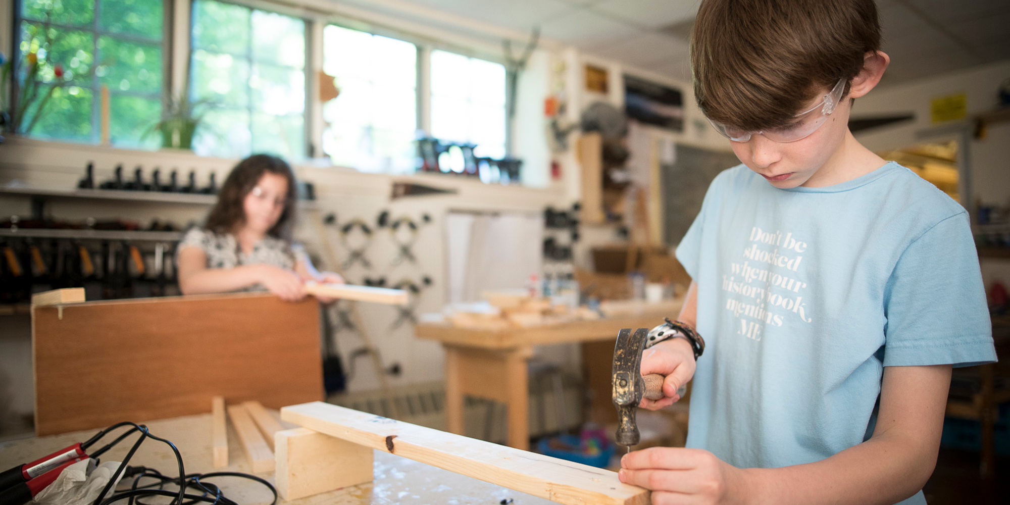 A boy in the woodshop hammers a project.