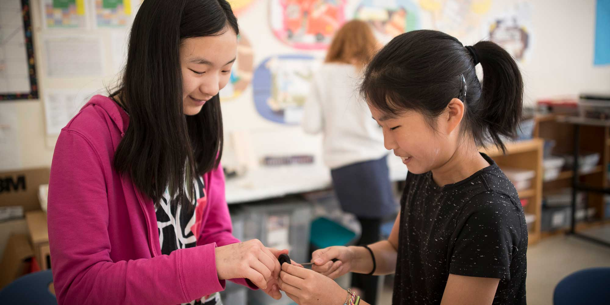 Two girls work on their solar car project