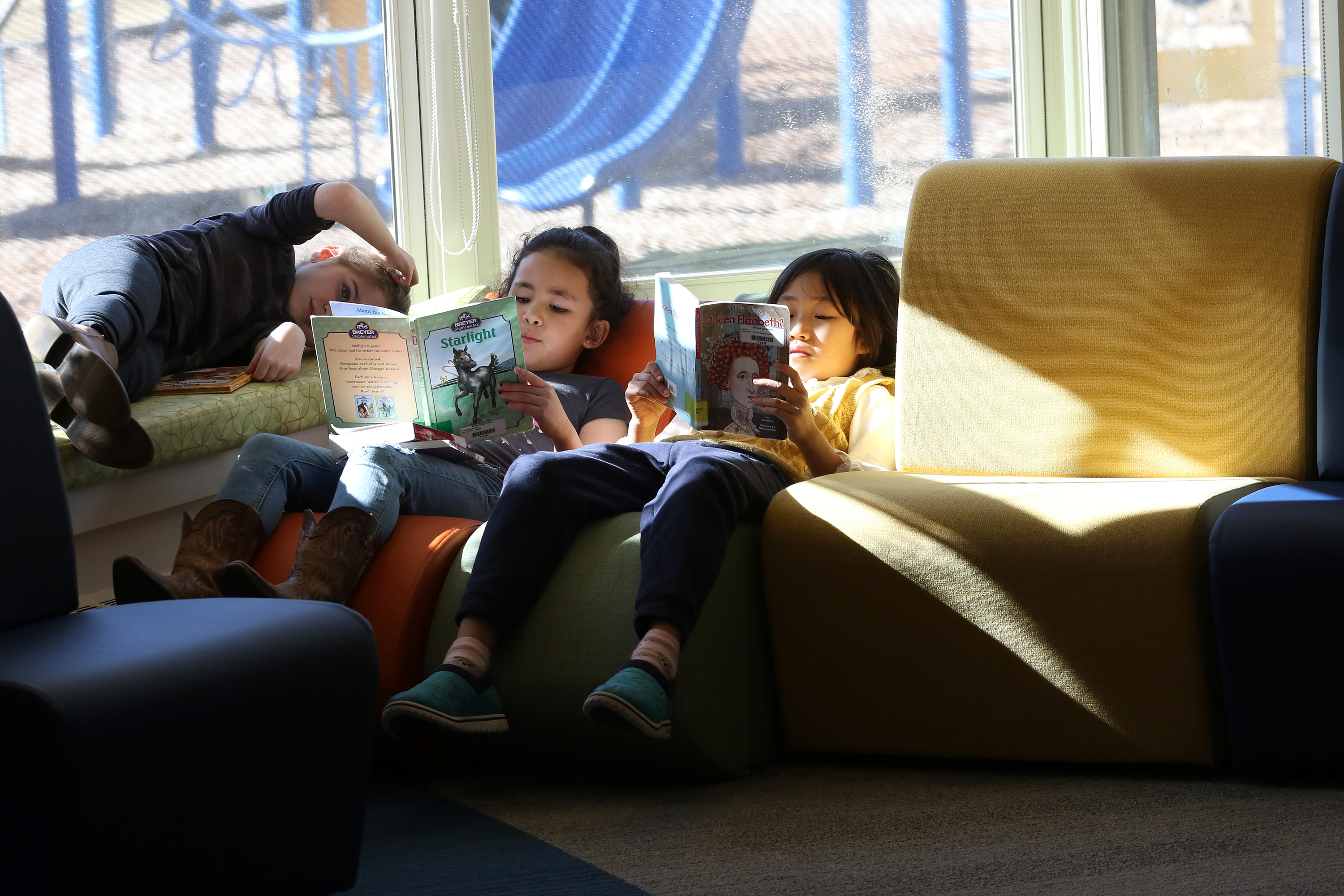 Three students reading in the sun in the Erskine Library