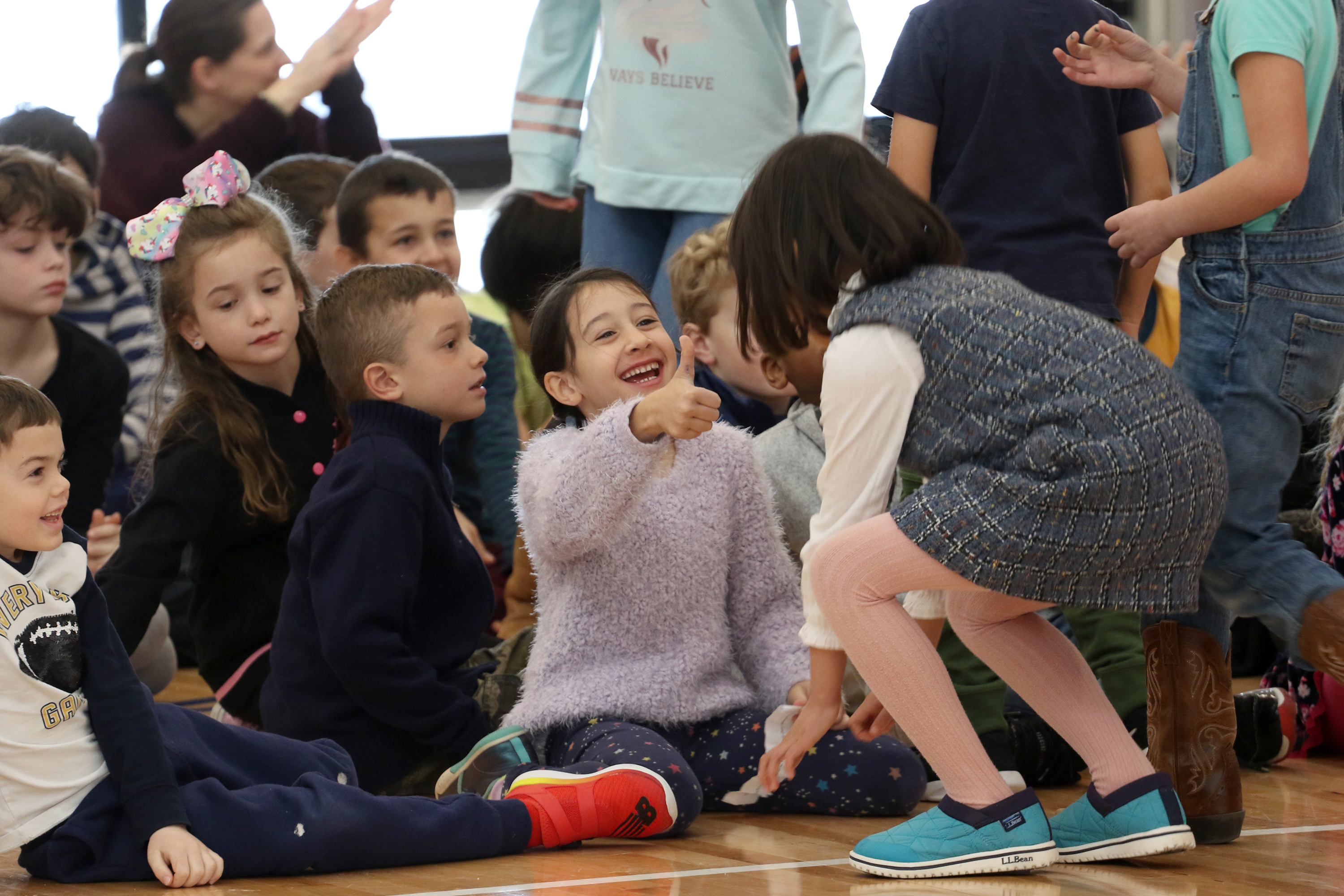 A student gives a thumbs up to a peer at sharing assembly