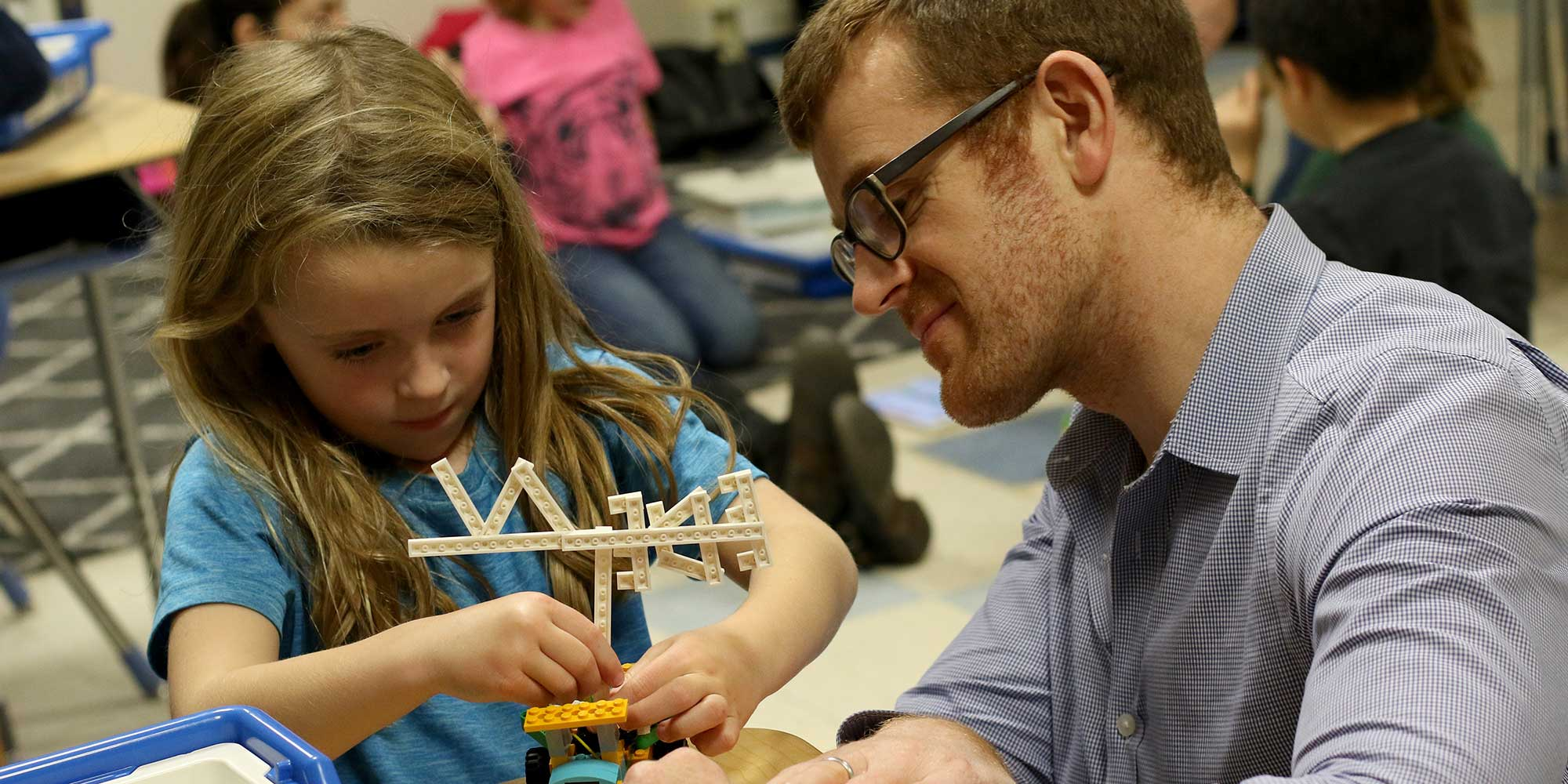 A dad and daughter work together on a Lego Robotics project