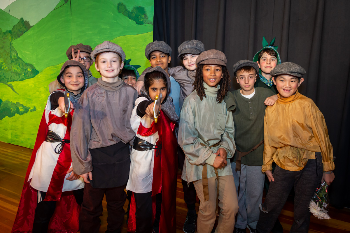 A group of boys in costume on stage during their class play