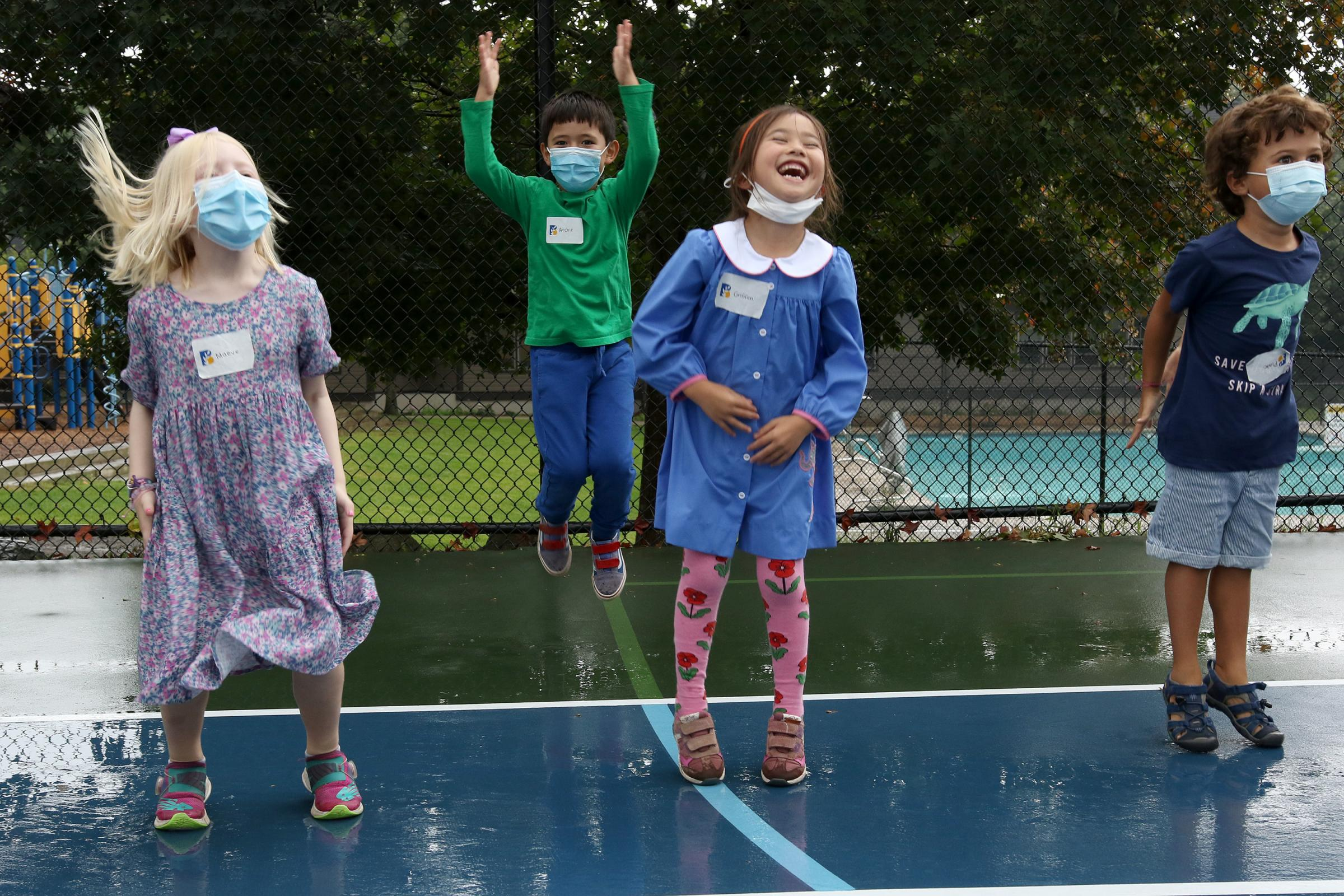 Four pre-k students laugh and jump together