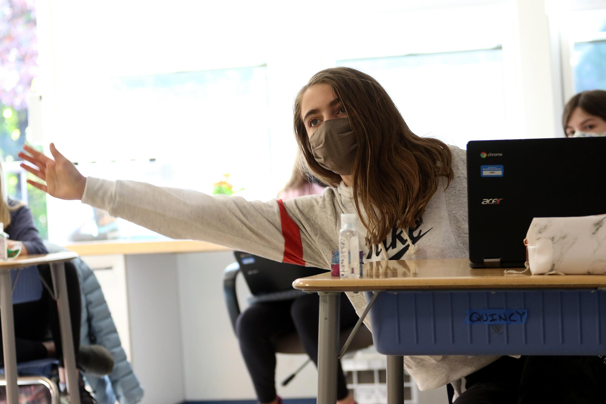 A student leans out of her chair raising her hand during a mock election