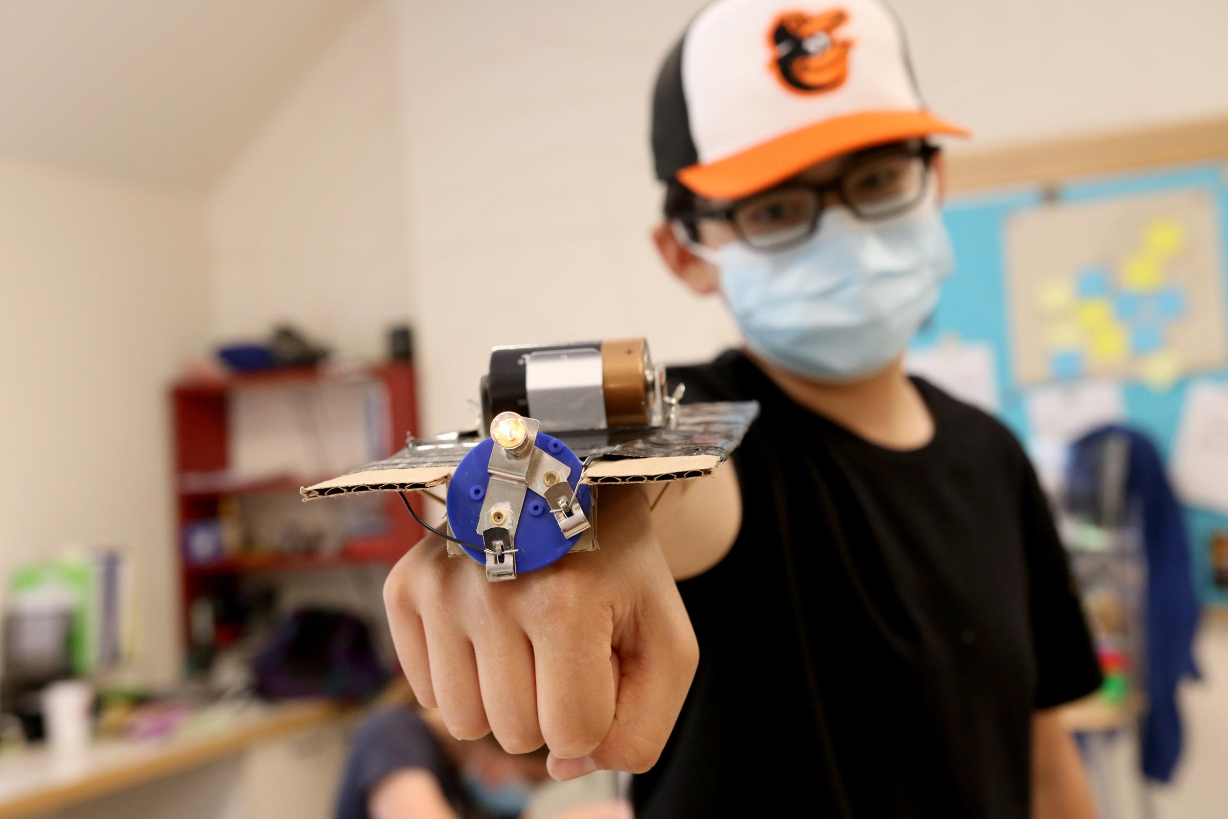 A student shows off the fitness tracker he built