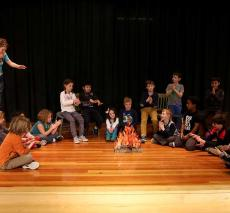 Students on stage rehearsing Camp Kindness