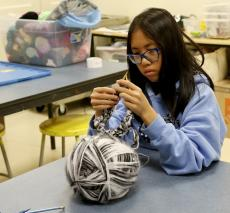 A student knitting.