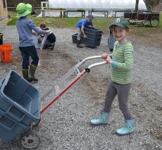 A girl wheels a bucket to be cleaned.