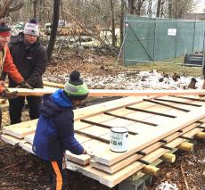 Volunteers help Mr. Smith mill oak trees for campus projects