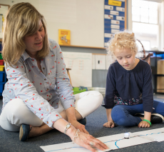 A first grader and her teacher use Ozobots technology