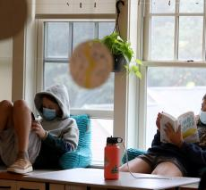 Middle School Students Reading Next To Windows