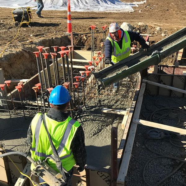 Pouring concrete into forms for field house footings