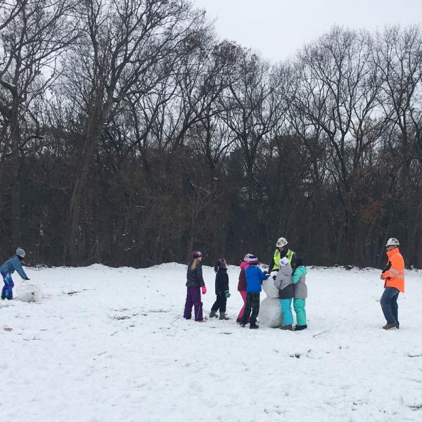 Shawmut construction workers give students snowman-building advice.