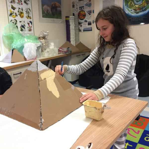 A student uses gold paint to design the exterior of her pyramid.