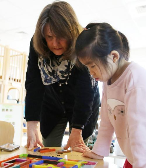 Pre-k teacher and students work on a math activity