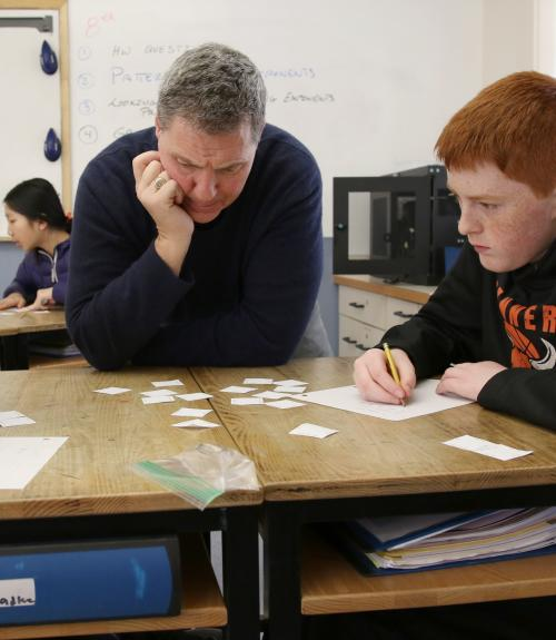 Math teacher RJ Parsons works on solving a math problem with two boys