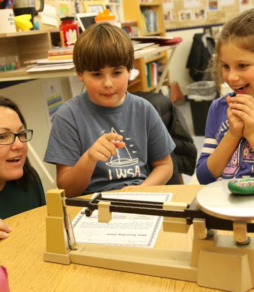 Two students share their math work with a teacher