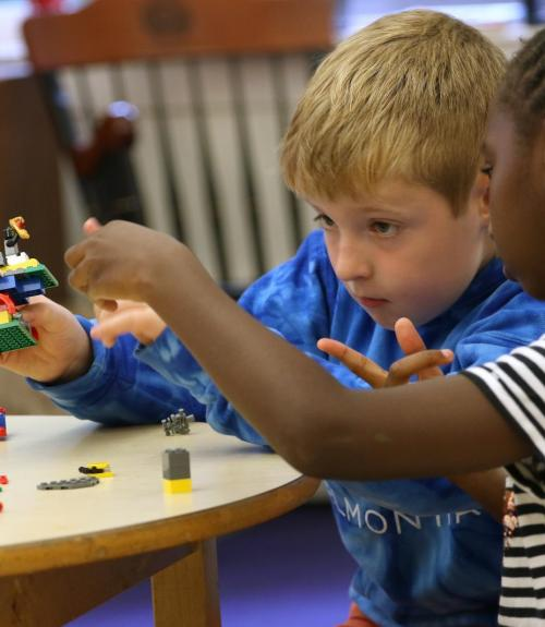Two students build a model with Legos