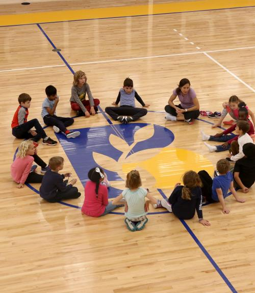 Students form a circle in the Barn gym with their teacher