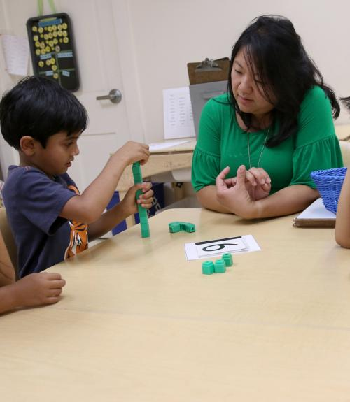 Kindergarteners and their teacher work with Unifix cubes