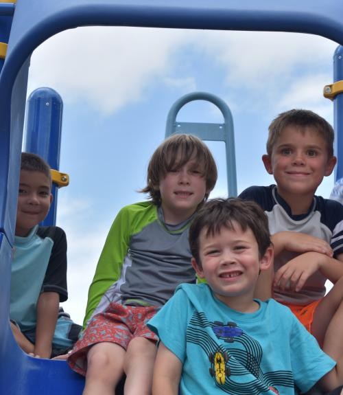 Four smiling boys on the camp playground equipment.