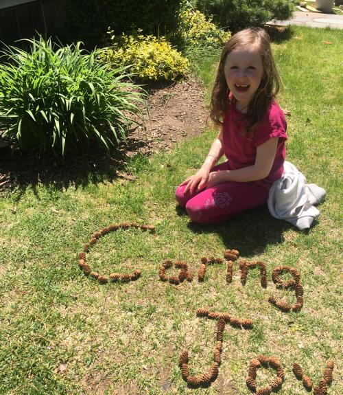 A girl writes the words caring and joy with pinecones