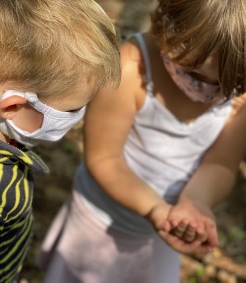 Two pre-k students in the garden holding a worm